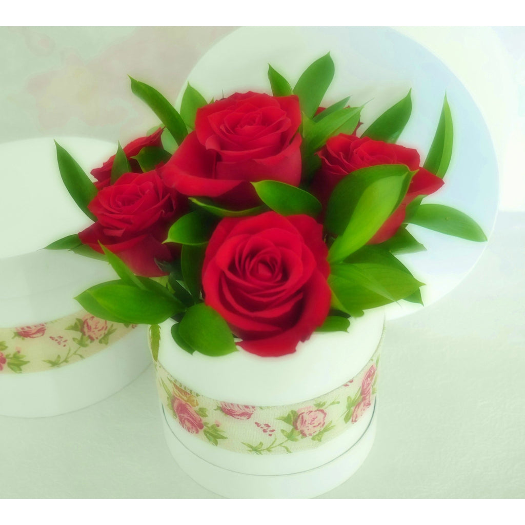"Linen Rose.  A vintage or cottage style arrangement of premium NZ red roses and superior foliage in a quality floral ""hatbox"" finished with a stylish linen rose sash."