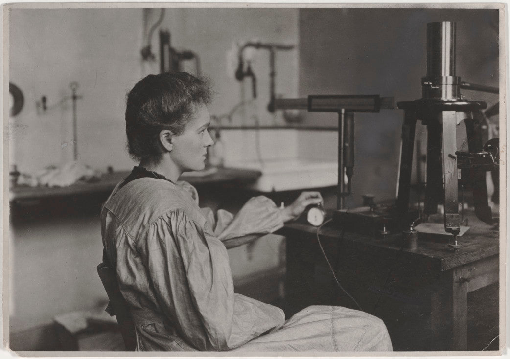 Marie Curie, chronomèter in hand, in the process of measuring radioactivity in the laboratory on Cuvier Street, 1904