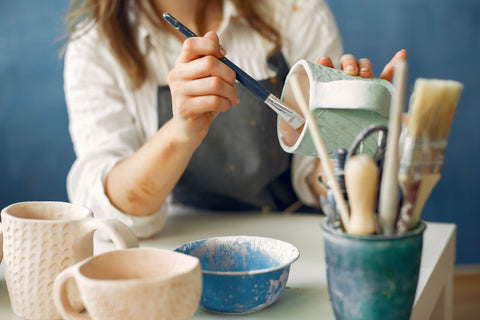 woman painting clay pot in pottery class
