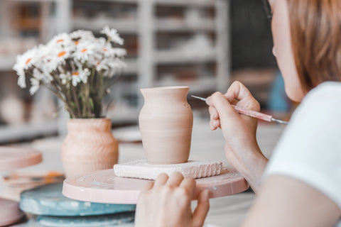 woman painting clay vase in pottery class