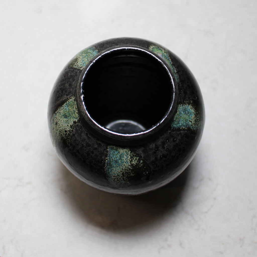 Aerial view of inside of small black and green pottery vase