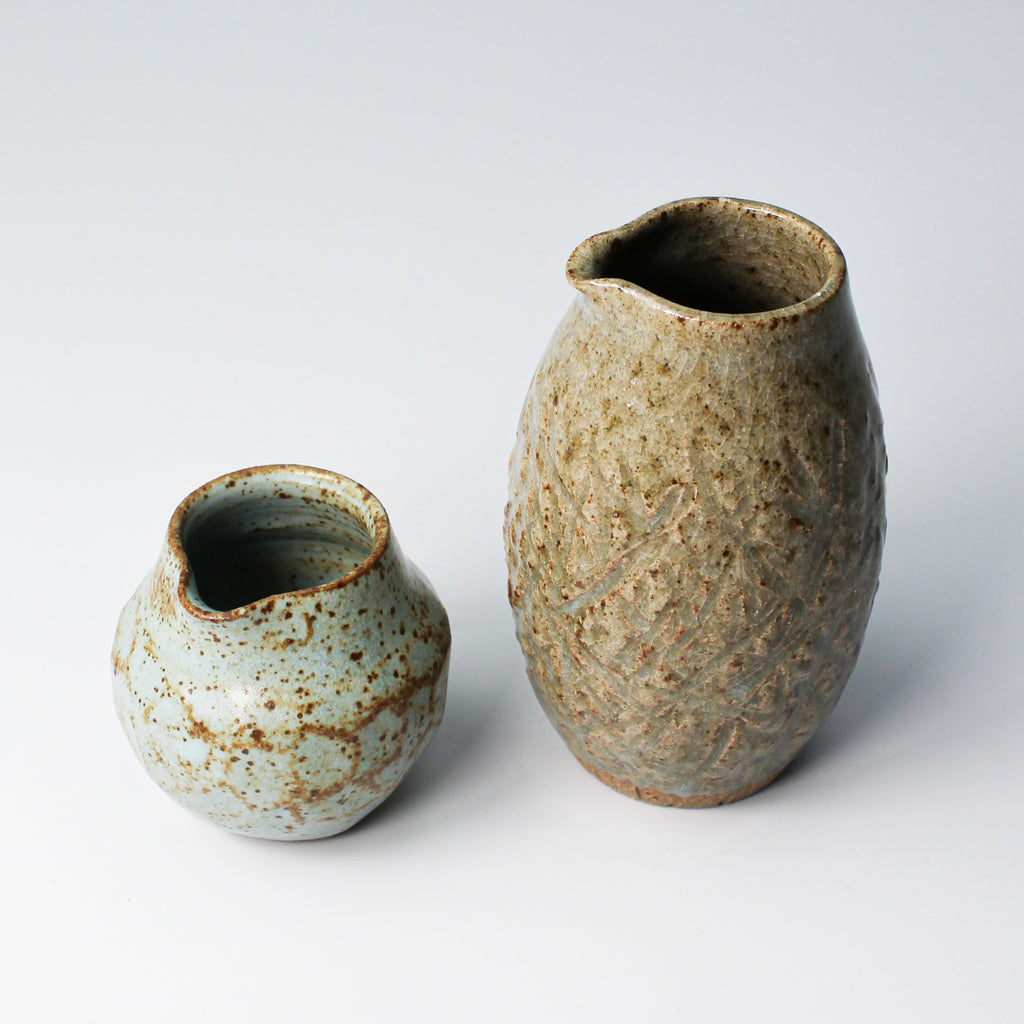 Two mini pottery jugs, one small round blue one and the other taller brown one
