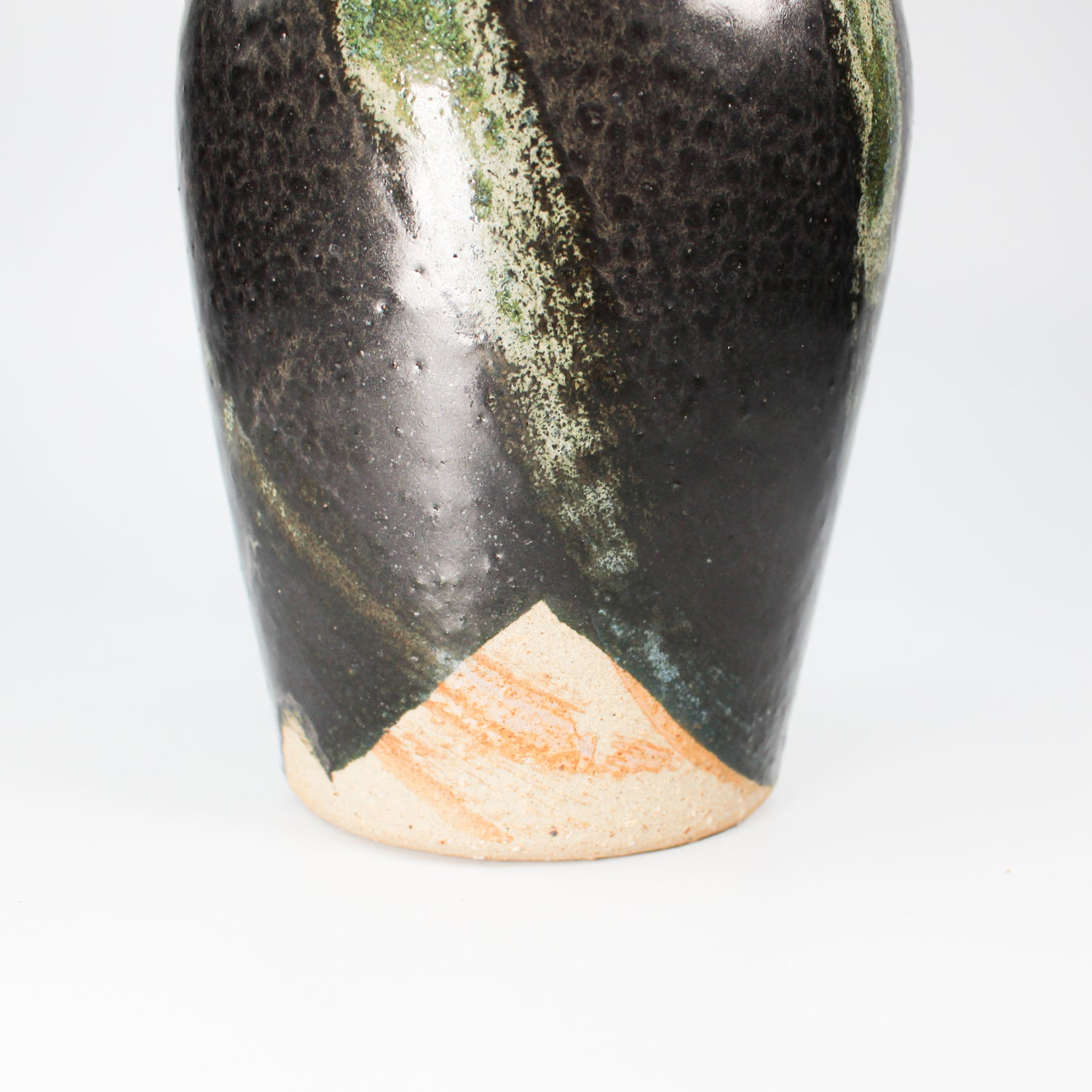 Bottom detail of small black and green pottery vase