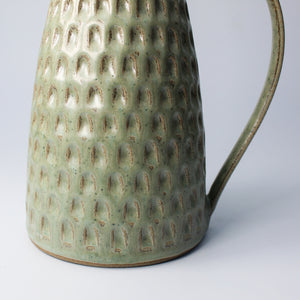 Bottom detail of stoneware jug with large handle