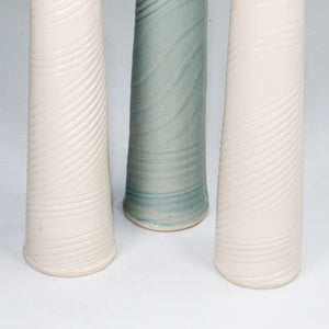Bottom of trio of porcelain vases. Two white. One baby blue.