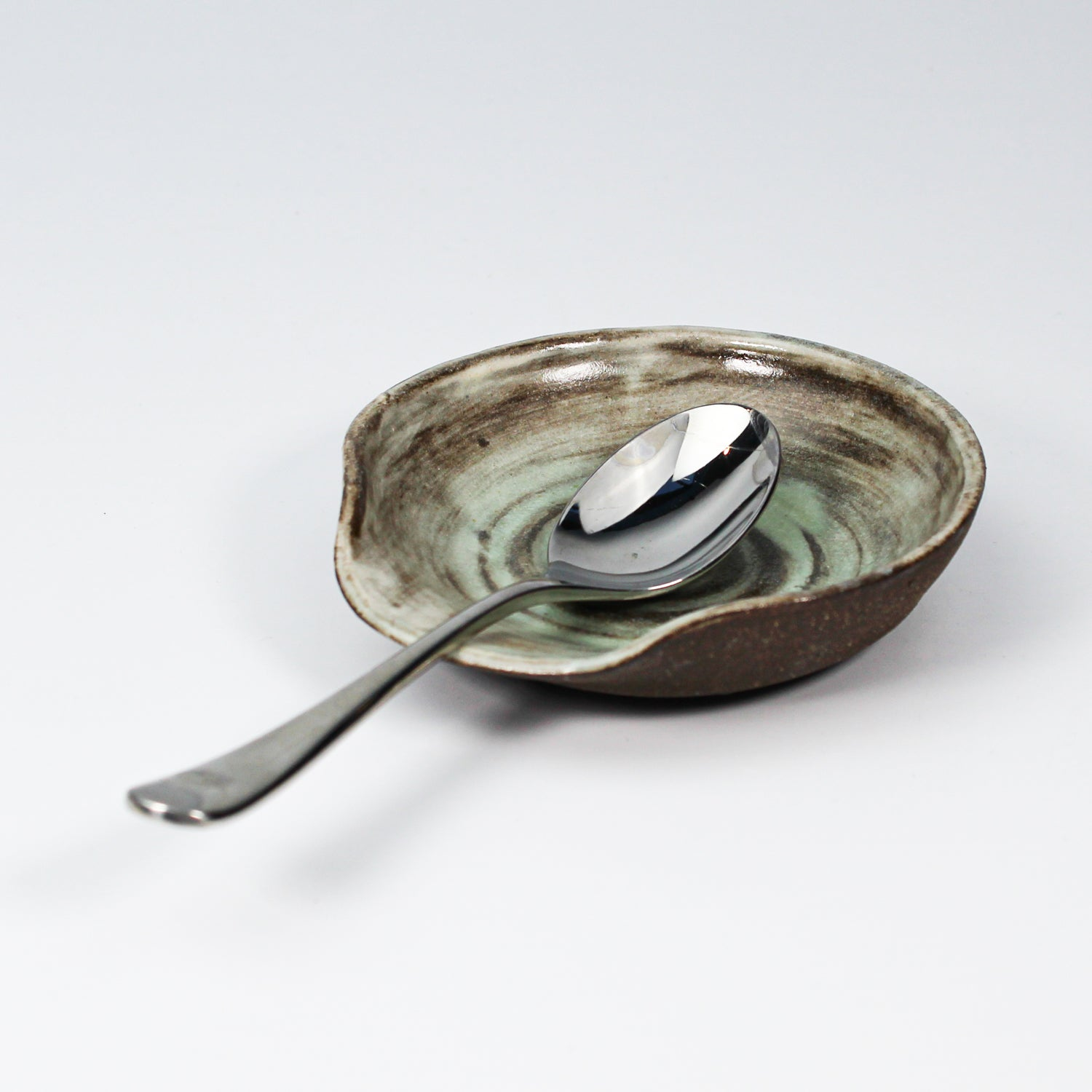 Ceramic spoon rest in brown and sage green with a teaspoon resting on it