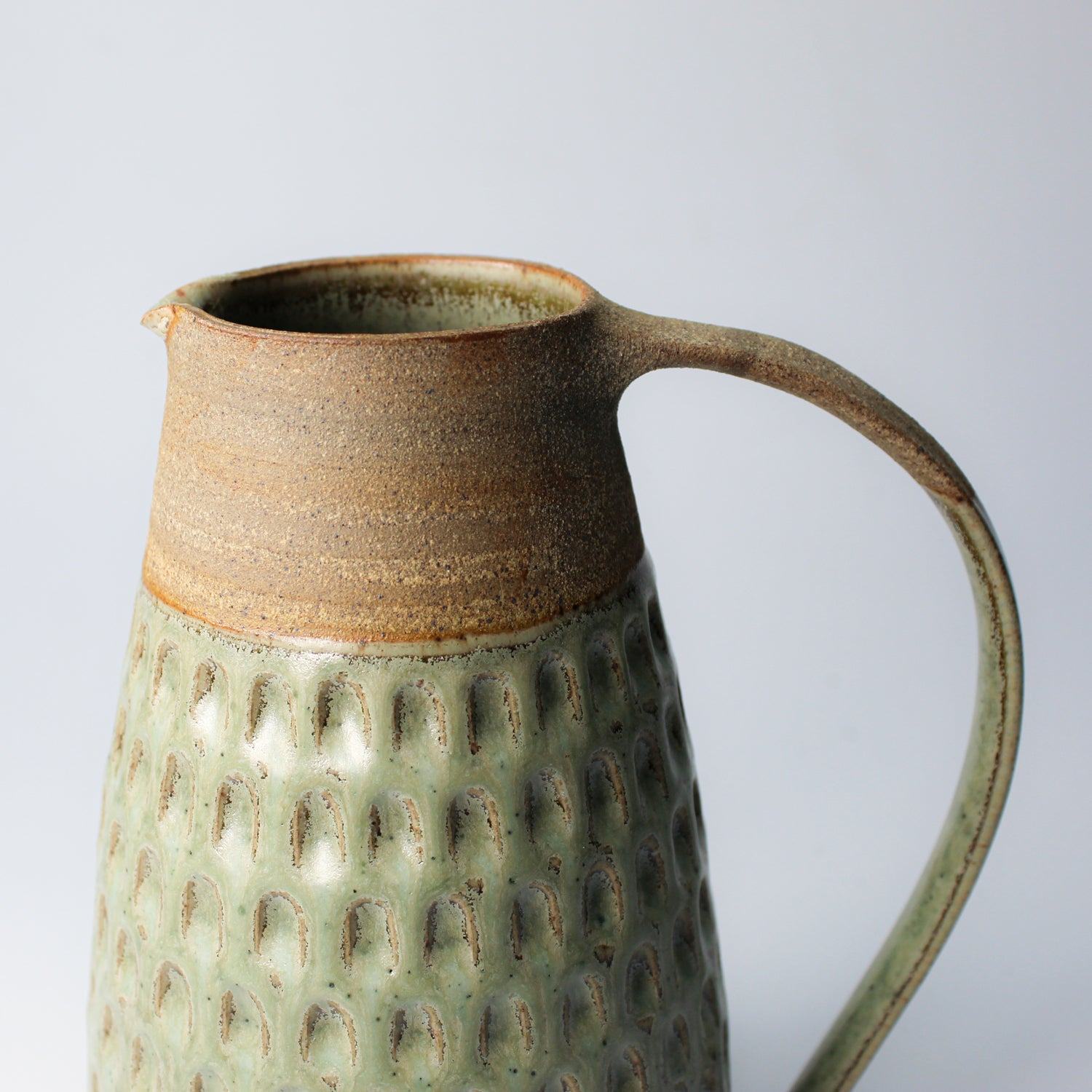 Top detail of stoneware jug with large handle. Top of jug has brown stripe