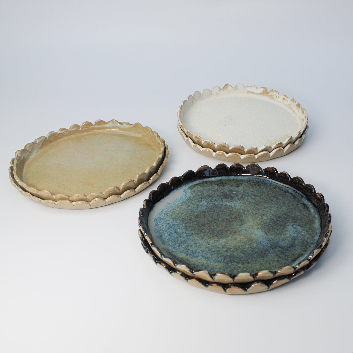 Three sets of two side plates with scalloped edges. One blue set, one white set and one sage green set.