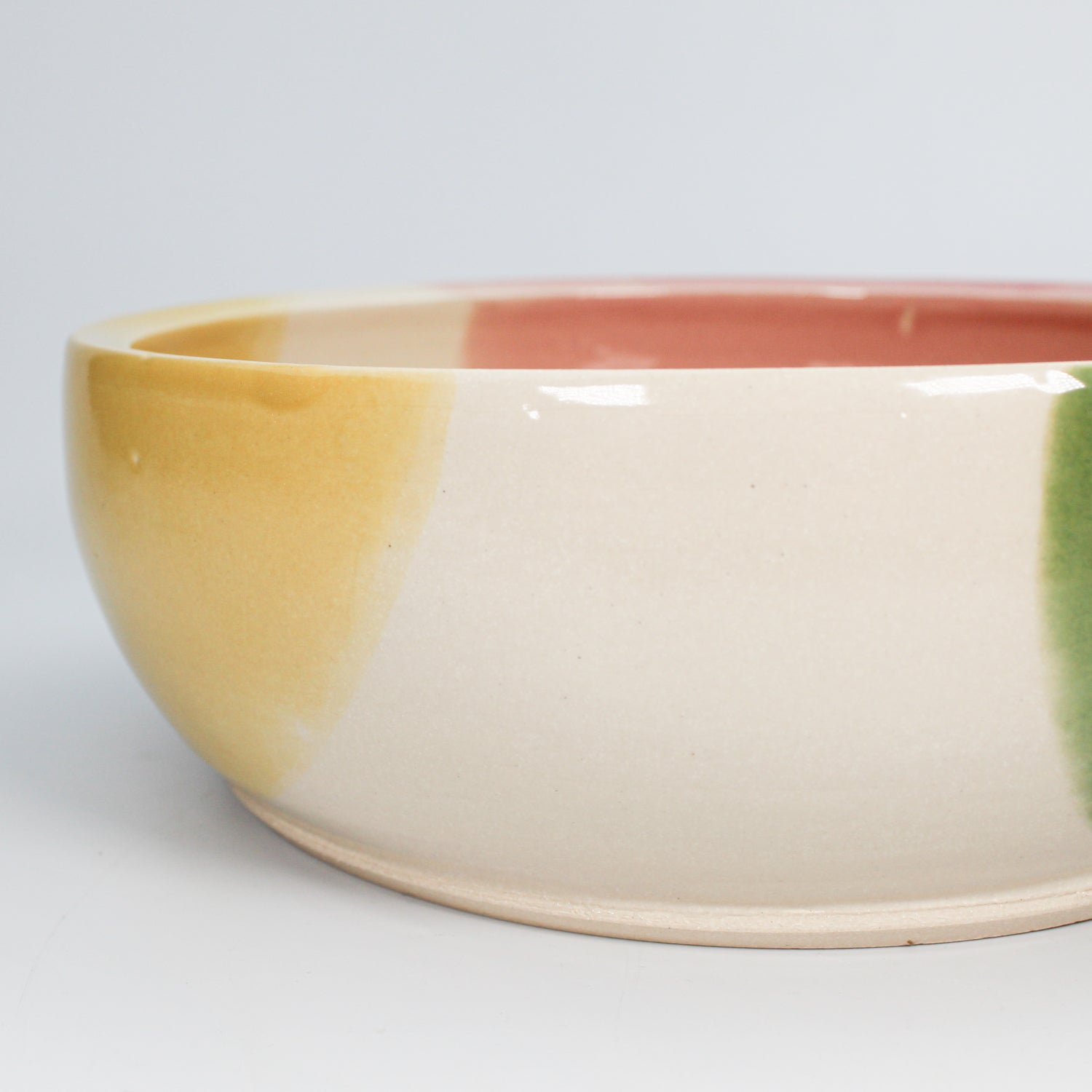 Close up of high gloss glaze detail on yellow, white, pink and green ceramic dog bowl