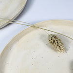 Load image into Gallery viewer, Close up of cream speckled ceramic side plate with dried grass on it