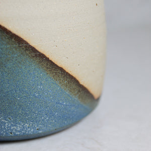 Close up of glazing detail on ceramic white and blue mug