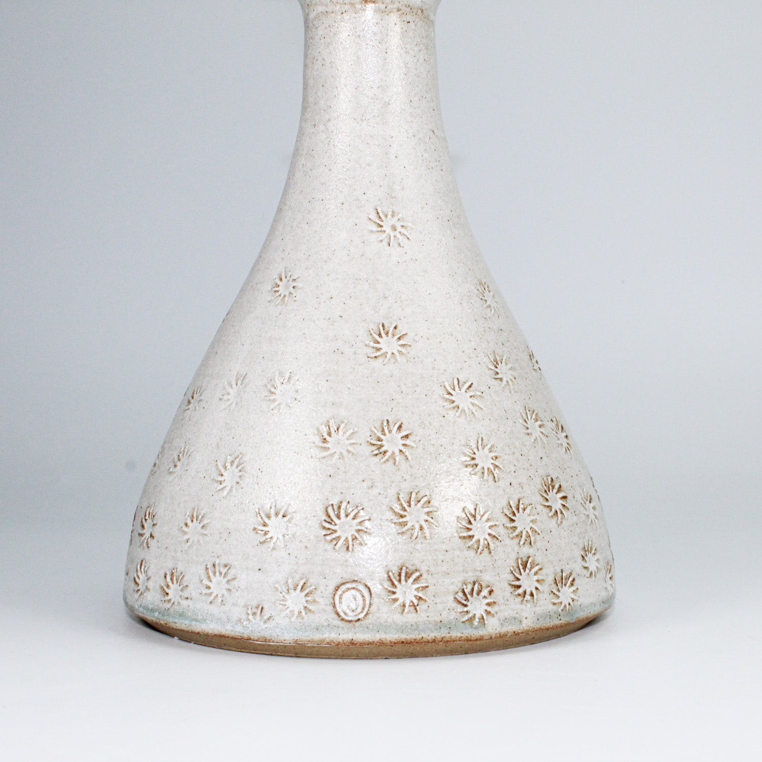 Close up of bottom of ceramic bottle vase with embossed detail