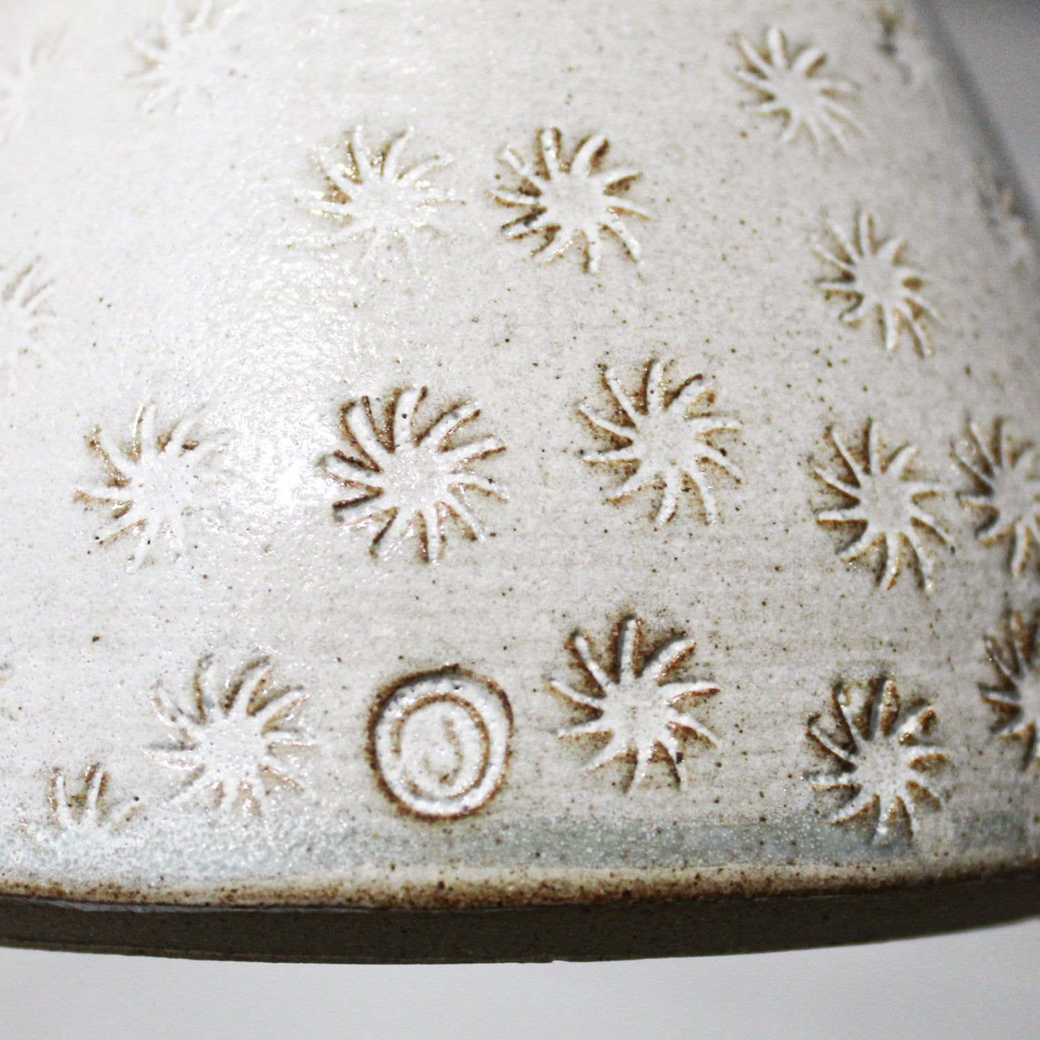 Close up of embossed detail on ceramic bottle vase