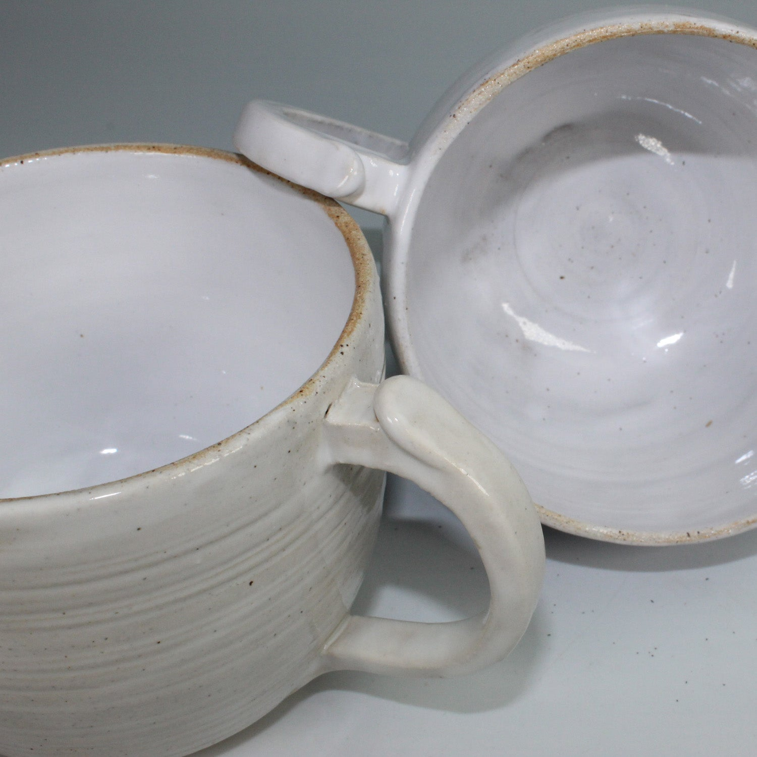 Pair of off white ceramic cups with one lying on its side