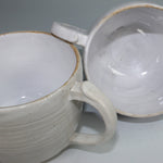 Load image into Gallery viewer, Pair of off white ceramic cups with one lying on its side