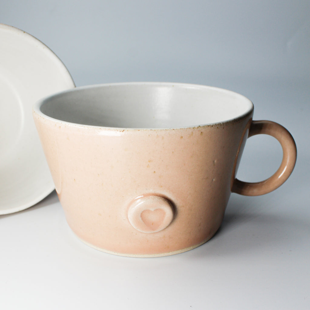 Pink pottery mug with heart motif and white inner