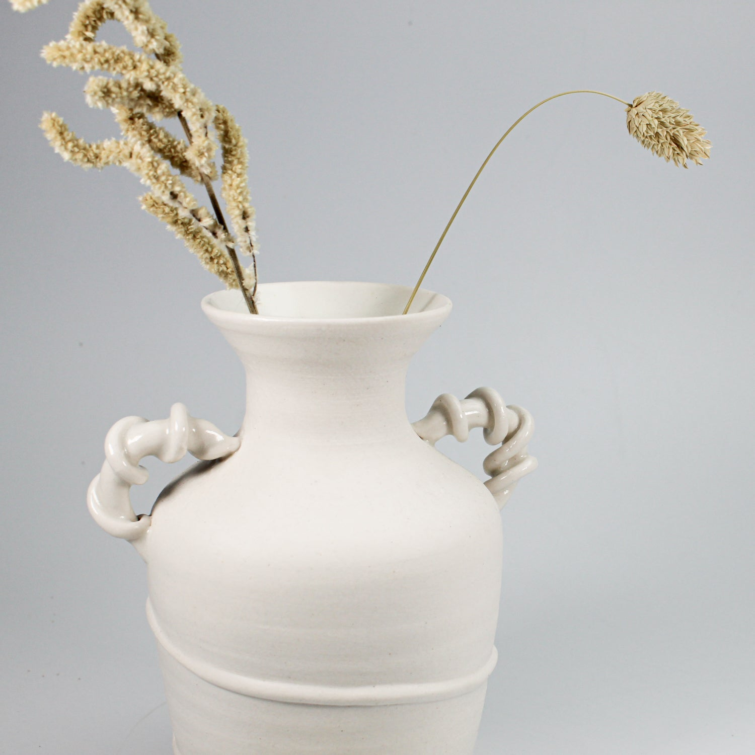 Top of small white ceramic vase with twisted handles. Dried grasses are displayed in it.