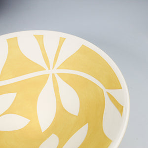 Close up of white leaf detail on yellow porcelain bowl