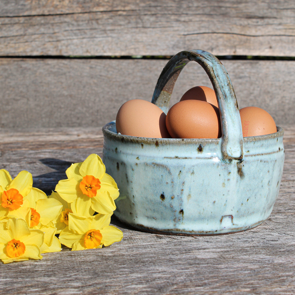 Ceramic baby blue and brown egg basket with eggs in and next to daffodils