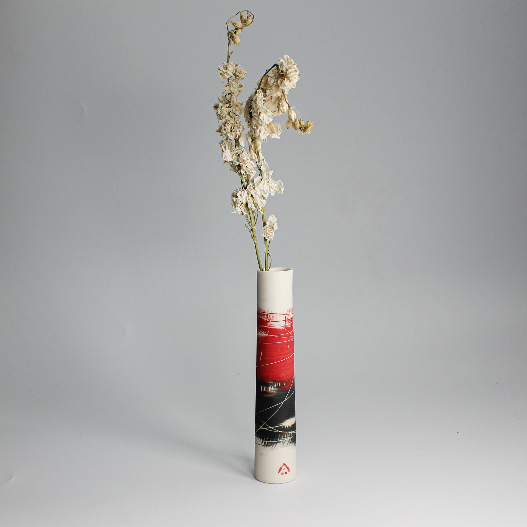 Red, white and black porcelain single stem vase