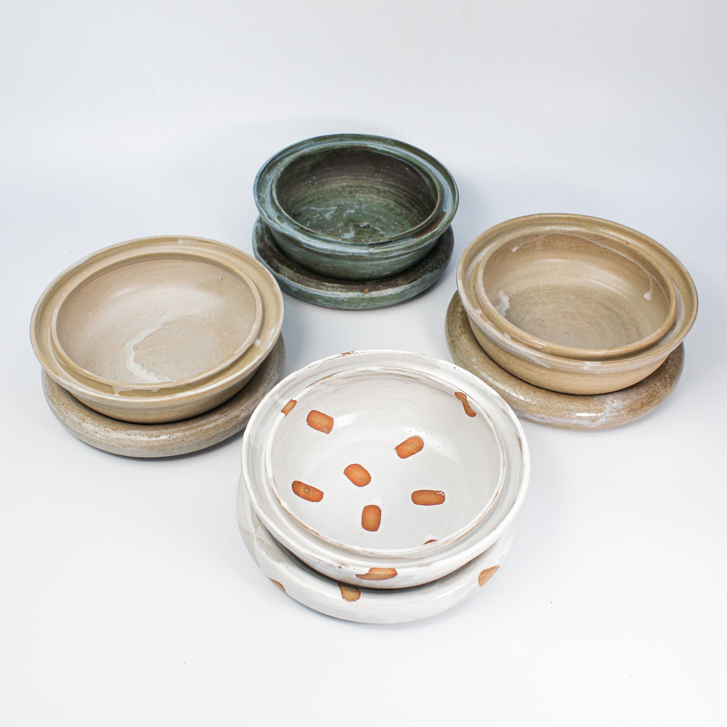 Set of four pottery dog food and water bowls. One in blue, one in natural gloss, one in natural matt and one in white spotted.