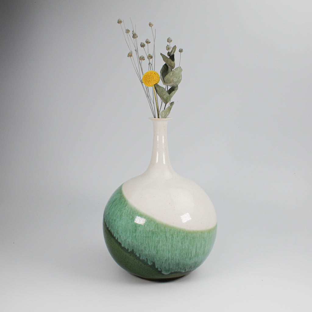 Green and white pottery vase with round bottom and narrow neck containing a few single flowers.