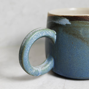 Handle of ceramic mug with half white and half blue glaze
