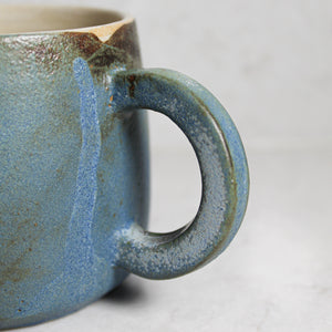 Blue handle of pottery mug with half white and half blue glaze