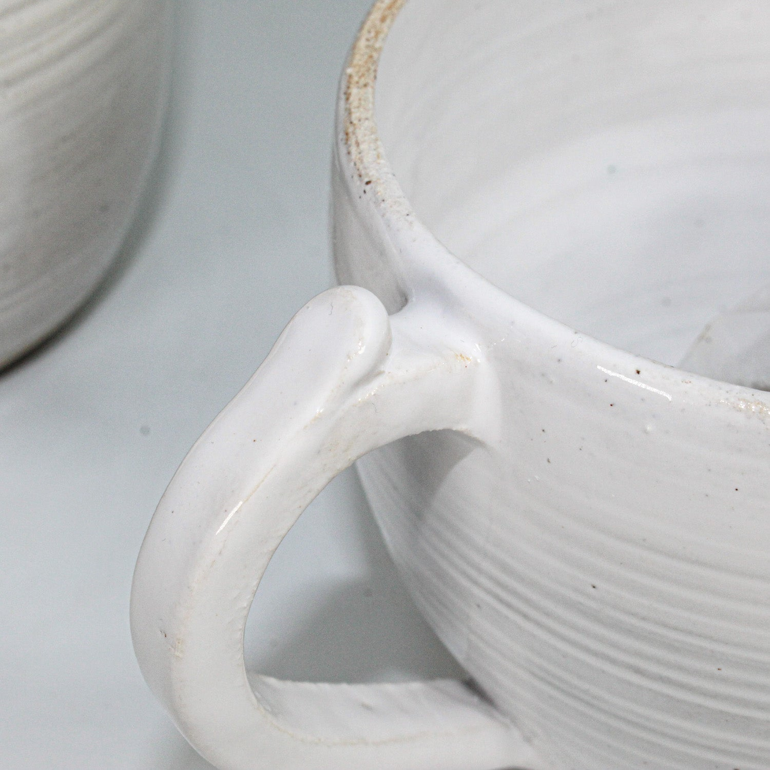 Close up of handle of off white ceramic cup