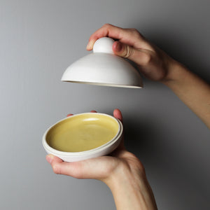 White pottery butter dish with mustard glazed inside. One hand is holding the top of  the dish and the other holding the bottom.