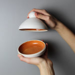 Load image into Gallery viewer, White pottery butter dish with orange glazed inside. One hand is holding the lid of the dish and the other is holding the bottom of the dish.
