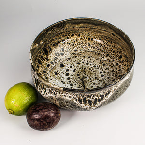 View from above of Japanese Croco bowl with fruit next to it. The glaze is brown and cream crocodile effect.