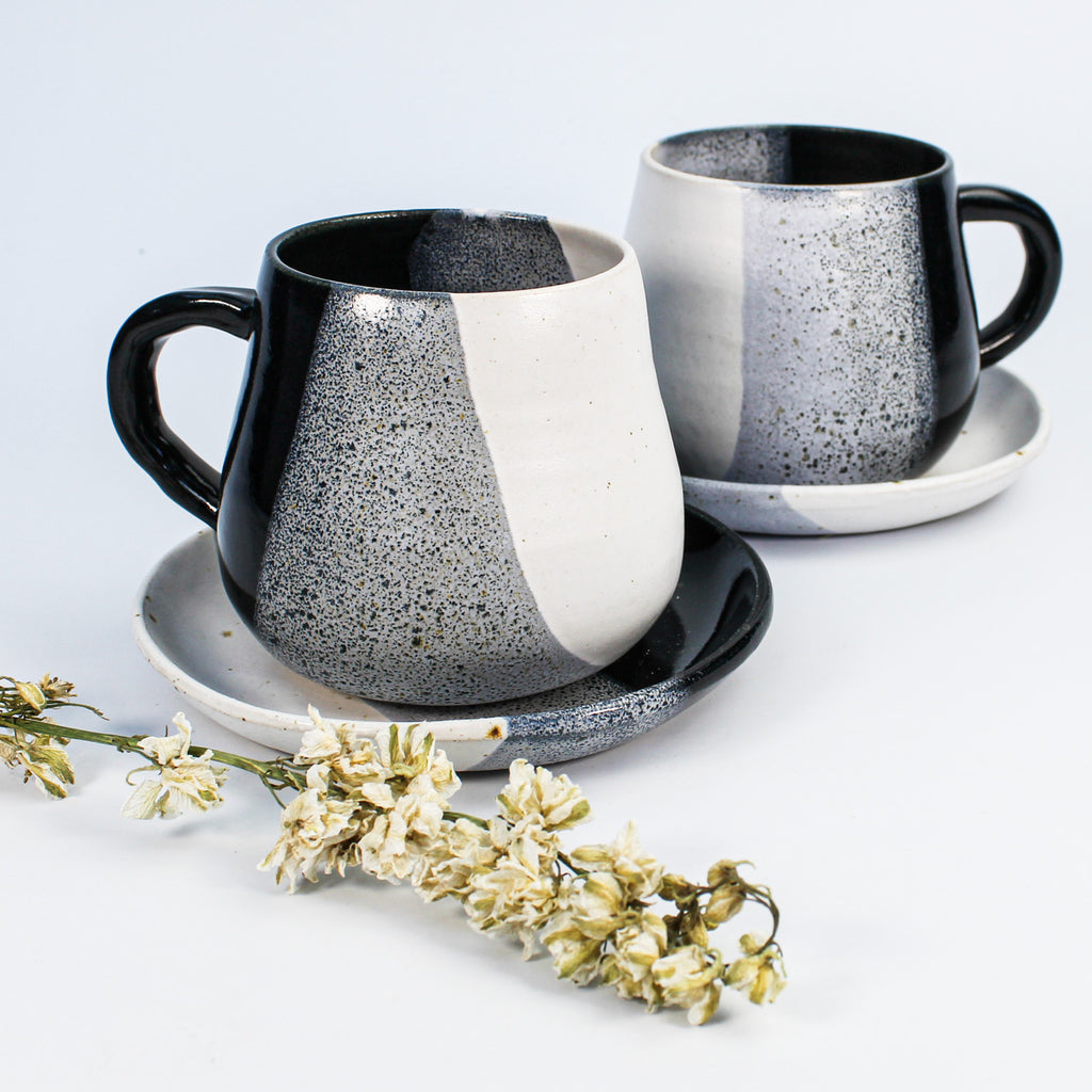 Two speckled grey, white and black pottery cups with matching saucers