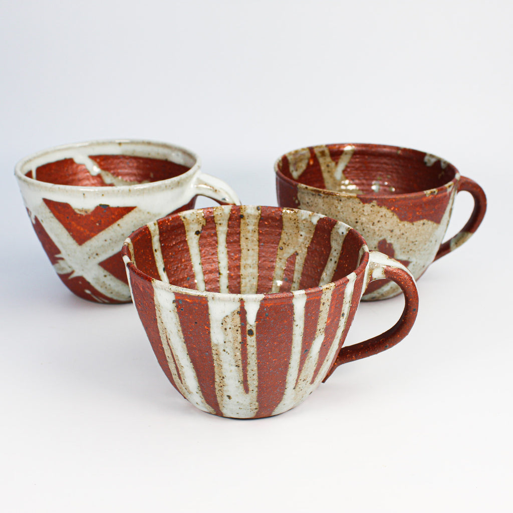 Three burnt dark orange and grey pottery soup mugs.