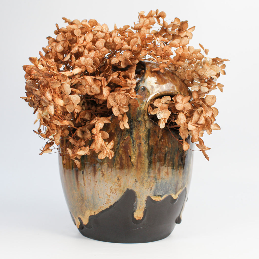 Black, gold and bronze openwork vase with dried flowers in.