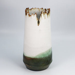 Large pottery vase with jagged top in white, bronze and green.