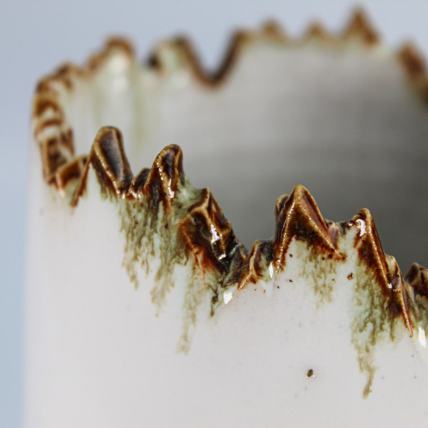 Close up of jagged brown glazed edge of large stoneware vase.