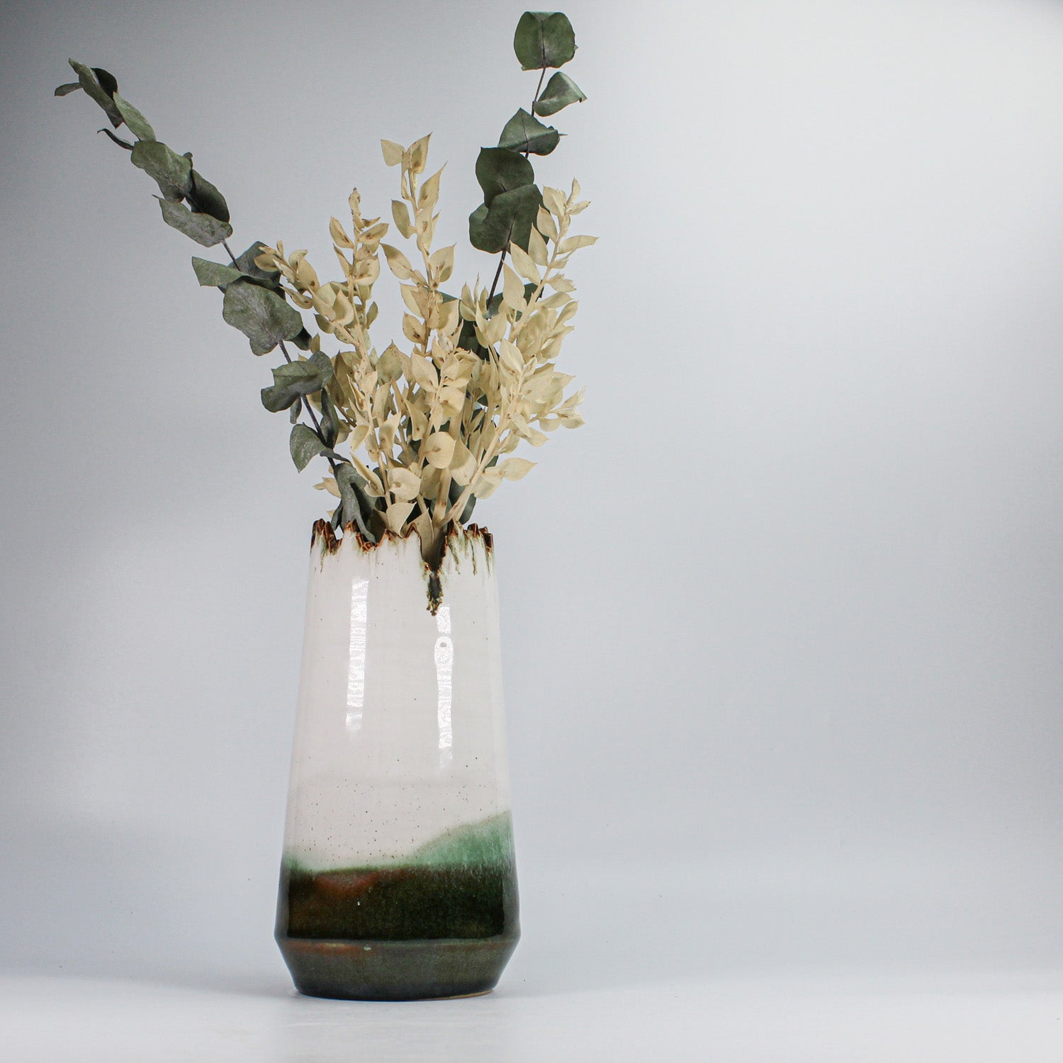 Large pottery vase with jagged top. White, green and brown. Dried flowers displayed within.