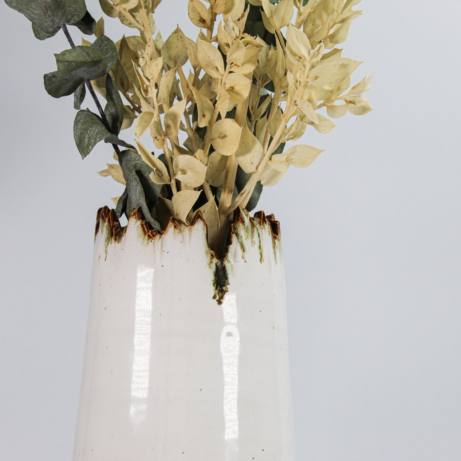 Top of large stoneware white, bronze and gold vase with jagged edge.  Containing dried flowers.