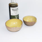 Load image into Gallery viewer, Two small ceramic pouring bowls with mustard yellow inside glaze. Next to a bottle of balsamic vinegar.