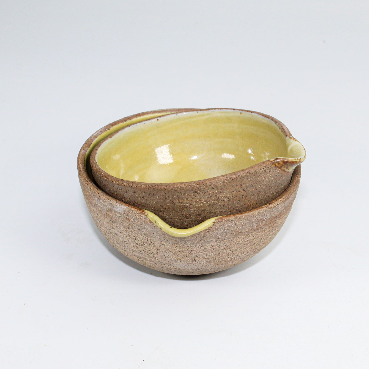 Pair of ceramic pouring bowls with mustard yellow insides. One stacked inside the other.
