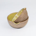 Load image into Gallery viewer, Pair of small ceramic pouring bowls with brown natural outer and mustard yellow inner. One bowl is tipped on its side inside the other.