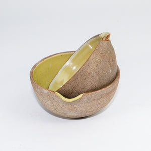 Pair of small ceramic pouring bowls with brown natural outer and mustard yellow inner. One bowl is tipped on its side inside the other.