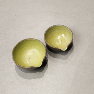 View from above of pair of ceramic pouring bowls. Mustard yellow inside with natural brown outer.