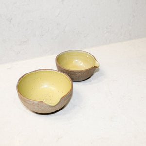 Set of two ceramic pouring bowls. Natural brown outer with mustard glazed inner.