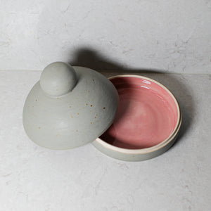 Aerial view of grey pottery butter dish with gloss glazed pink inner. Lid off
