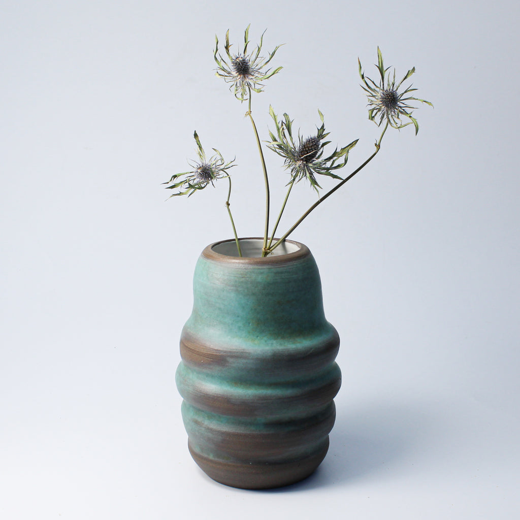 Jade green and brown ceramic vase with dried flowers in