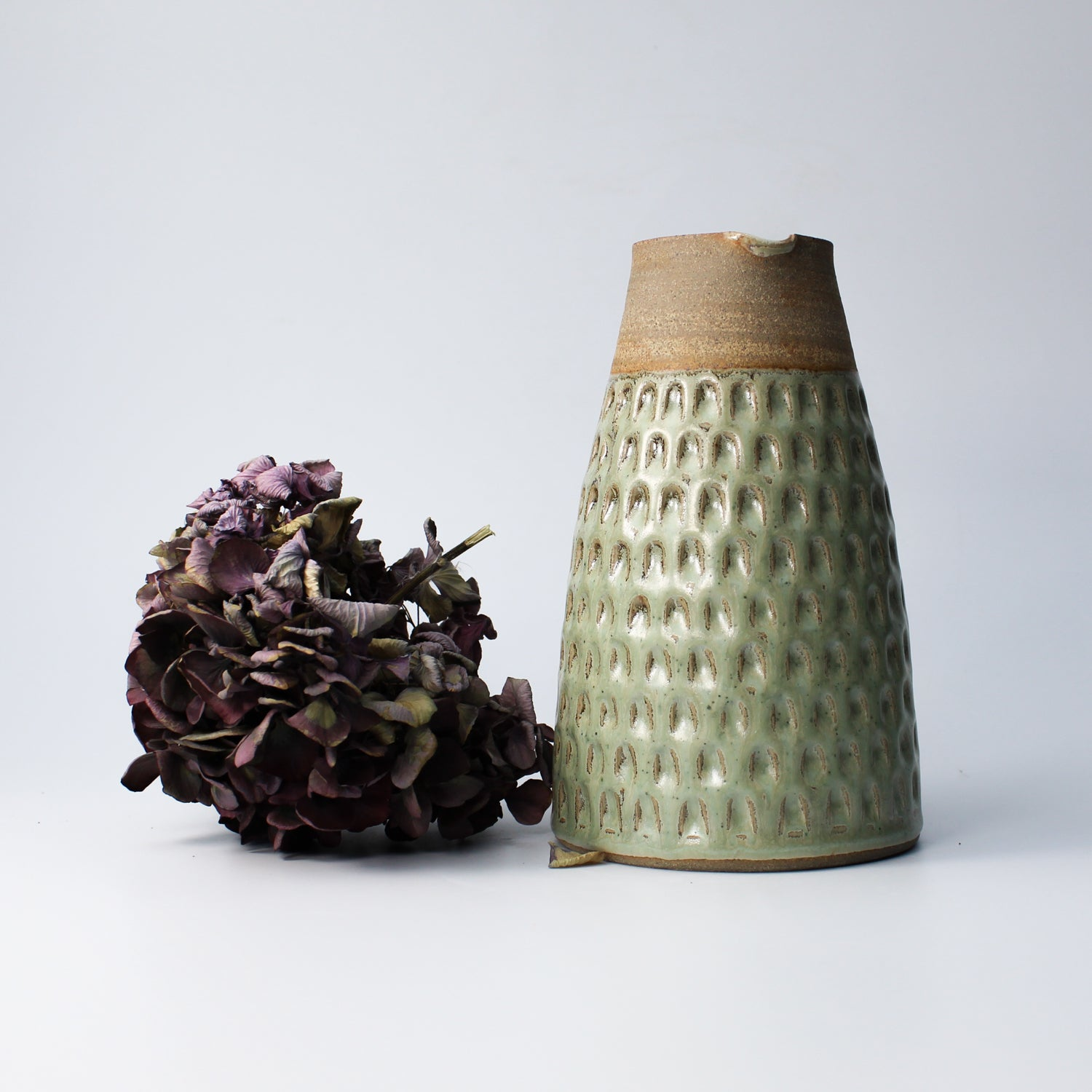Green and brown stoneware jug next to dried purple flower head