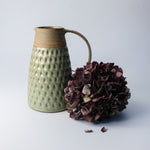 Load image into Gallery viewer, Green and brown stoneware jug next to dried purple flowers