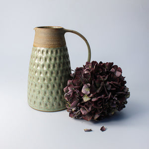 Green and brown stoneware jug next to dried purple flowers